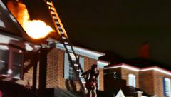 Fire fighter stepping halfway on a ladder leaning on house on fire - Commercial Stock Footage