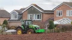 Green Tractor and Equipment on Ploughed Field on Rural Farm Stock Footage
