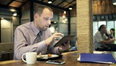 Unhappy businessman with smartphone and tablet reading bad news in cafe HD - stock footage