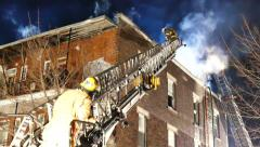 Firemen attending building fire at night with jacked up ladders - Commercial Stock Footage