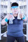 Obese man drinks water at gym - stock photo