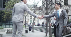 4K Young Asian business group meet and shake hands outdoors in the city Stock Footage