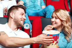 Pair of people sharing popcorn - stock photo