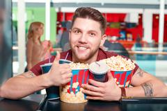 Young man buying popcorn and coke - stock photo