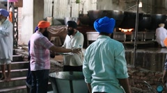 Poor sikh people clean dishes at soup kitchen in Golden Temple, Amritsar, India Stock Footage