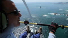 AERIAL SHOT-BACK SHOULDER. Ultralight aircraft pilot flying over the coast. Stock Footage