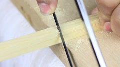 Piece of plank is cut by hand using a back saw. Stock Footage