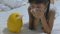 Little Asian child sick with flu sneezing and clean with tissue paper - stock footage