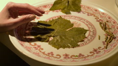 Housewife rolling grape leaves with rices traditional Turkish food; Yaprak dolma Stock Footage