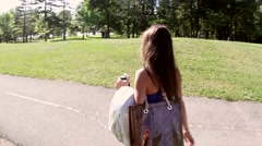 Beautiful girl walks through park in summer Stock Footage