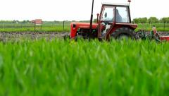 Red tractor in a field planting corn Stock Footage