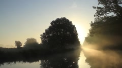 Early morning in fall, sunrise and fog at a river Stock Footage