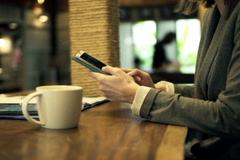 Businesswoman hands texting on smartphone sitting in cafe NTSC - stock footage