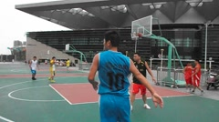People playing basketball in Shenzhen, Baoan stadium, China Stock Footage