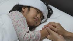 Asian child sick and sleeping on the bed with her mother by her side. - stock footage
