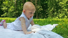 Little girl lies on a white cover on a green grass in summer day Stock Footage