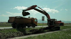 Excavator digging canal and loading dumper with ground, street reconstruction. Stock Footage