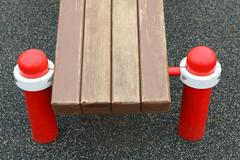 Bench of an outdoor children sport complex in the court playground Stock Photos