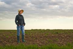 Female Farmer Standing on Fertile Agricultural Farm Land Soil - stock photo