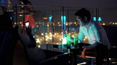 EDITORIAL Couple with smartphone sitting on terrace in bar at night HD Stock Footage