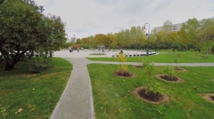 People walk by square around Dry Fountain in Lilac Garden Stock Footage