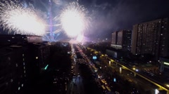 Sparks of fireworks and projectors rays in dark sky near TV tower - stock footage