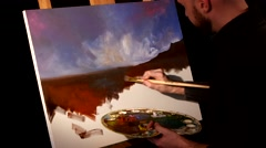 Stylish painter goes on drawing a new painting with sky and ground by oil paints Stock Footage