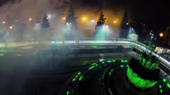 Fountain adorned by garlands on ice rink with people - stock footage