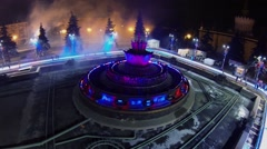 Empty fountain adorned by garlands on skating rink with people Stock Footage