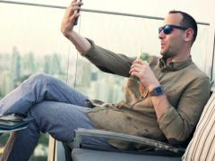 Happy man with cocktail taking selfie photo with cellphone in sky bar NTSC Stock Footage