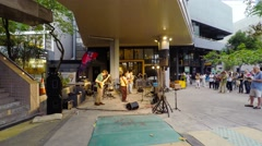 Young street musicians play rock'n'roll on open air in Hong Kong. Stock Footage