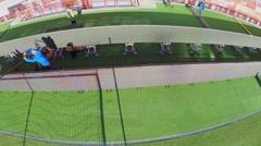 People work near grass field with gate on football stadium Stock Footage