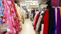 Walking in passage at colourful fabric market, thousands of textile products Stock Footage