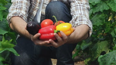 Guy demonstrates the organic vegetables directly to the camera Stock Footage