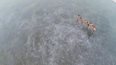 Chain of naked young men and women skate on icy pond Stock Footage