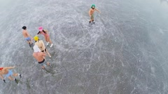 Naked young men and women skate on icy pond at winter - stock footage