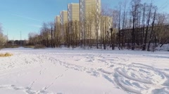 Snowbound lake with trails not far from residential complex Stock Footage