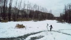 Woman skating by icy pond among snow at winter evening. Stock Footage