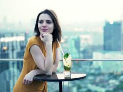 Portrait of happy woman drinking cocktail standing on terrace in sky bar NTSC Stock Footage