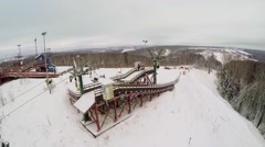 Chairlifts moves people along snow slope at winter cloudy day Stock Footage