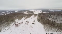 Snow slope with people and ropeway among forest at winter Stock Footage