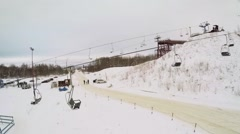 Stock Video Footage of Empty chairs of ropeway moves on small hill covered by snow