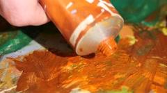 Painter squeezes orange oil paint on a palette, close up, slow motion Stock Footage