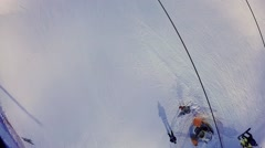 Chairlift moves people above snow slope at winter evening. Stock Footage