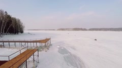 People ride by snow not far from wooden pier in icy river Stock Footage