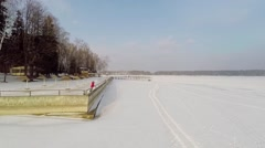 Woman stands on quay of snowbound river Istra at winter Stock Footage