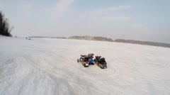 Helicopter flies above river where men prepares snowmobiles Arkistovideo