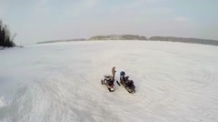 Two men prepares snowmobiles for ride by snowbound icy river Stock Footage