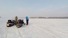 Two men in helmets stand near pair of snowmobiles Arkistovideo