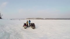 Two men stand near pair of snowmobiles not far from people Arkistovideo
